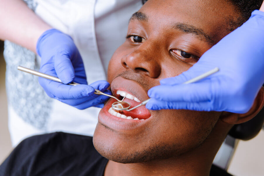 endodontist African male patient getting dental treatment in dental clinic